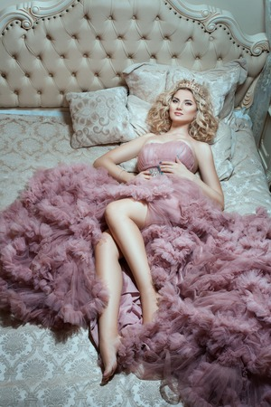 sumptuousness: Girl in pink dress lying on a lush bed. Top view of the bed.