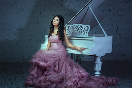 In a dark room girl sitting at a white grand piano.