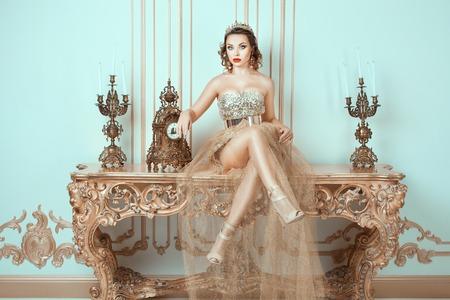 couronne royale: Fille avec une couronne sur sa t�te assis sur une vieille table. Son image de la mode de la reine.