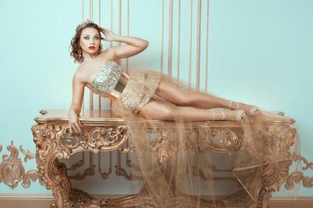 corona de reina: Mujer de moda se encuentra en una mesa antigua caro. Ella es la Reina con una corona en la cabeza. Foto de archivo