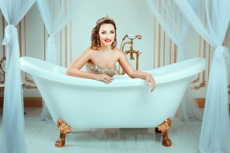 sumptuousness: Girl with crown lies in the bath and smiling. Her bright makeup, its fashion style. Stock Photo