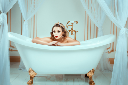 sightly: Nude woman sitting in expensive jewelry bath. Crown on his head, his face bright trendy makeup.
