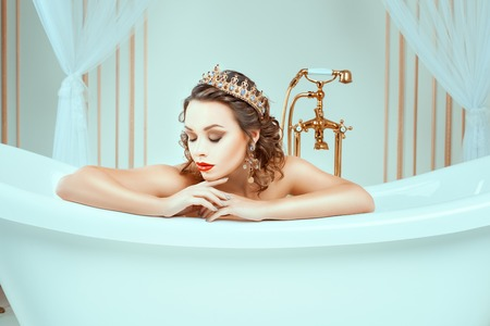 naked woman sitting: Beautiful naked young woman sitting in expensive jewelry bath. In the face of a bright fashion make-up on her head a crown. Stock Photo