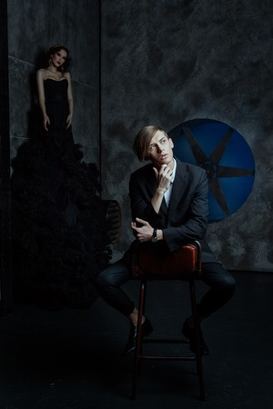 lunacy: Fashion man sitting on a chair in a room and dreaming. Behind him, a woman in a black dress. Stock Photo