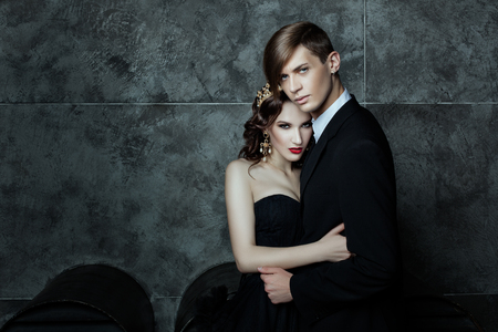 beguin: Boy and girl standing in an embrace, her crown on his head. Fashionable and stylish couple for a fashion magazine.