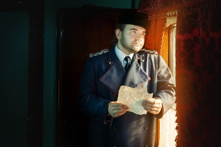 ruminate: Sad retro man standing near the window. He carried an old manuscript. Sad eyes stare out the window. The manuscript is not legible handwriting. Stock Photo
