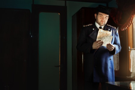 missive: Man in retro uniform stands at the window, holding the manuscript. He sad eyes reading a letter. The manuscript is not legible handwriting. Stock Photo