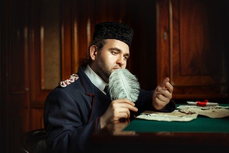 ruminate: Man wrote the manuscript with a quill pen in retro style. It retro form last time. The manuscript is not legible handwriting. Stock Photo