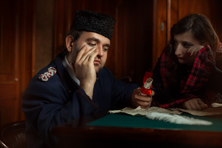 missive: Man and woman in retro style weep over the manuscripts. The main character of the man, the woman is blurred in the background.