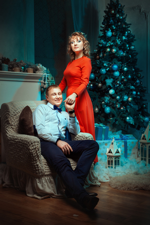 smartness: Man sits in a chair and holding a womans hand. The room is decorated Christmas tree.