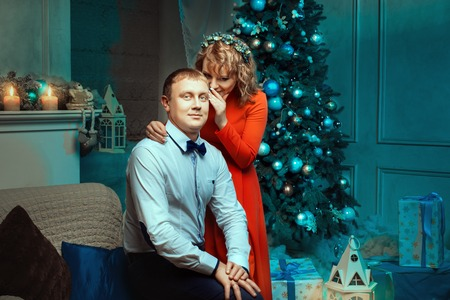 smartness: Woman whispering in the ear of a man gentle words New Years Eve near the Christmas tree ornaments. Stock Photo
