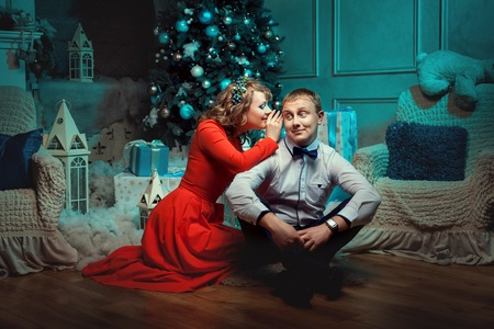 female christmas: Woman whispering in the ear of the man. They married young couple. Gifts under the Christmas tree. Stock Photo