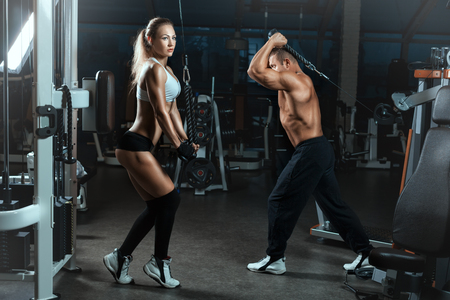 exercitation: Girl and the man go in for sports in the hall with machines for bodybuilders. They lift heavy weights to build muscle.