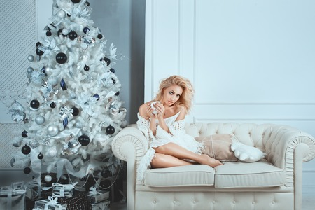 smartness: Cute girl sitting on white sofa near the Christmas tree. In her hands she holds a cup and drink. Stock Photo