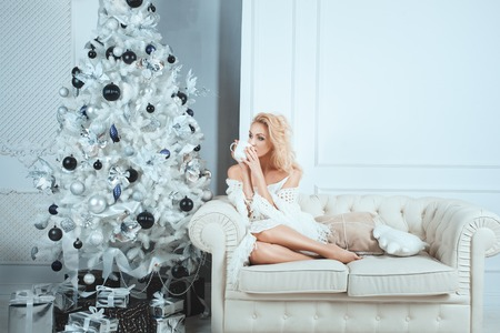 smartness: Girl drinks from  mug near a Christmas tree. Under the tree are gifts for Christmas.