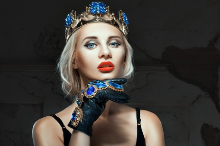 Girl with a crown on his head and blue eyes. Close-up portrait.