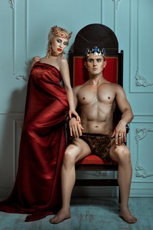 siervo: Hombre rey sentado en el trono al lado de la reina es una mujer. El hombre es fuerte y dominante. Foto de archivo