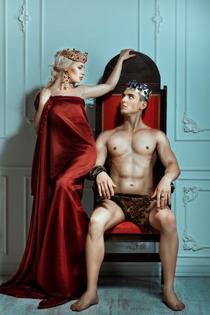 siervo: El hombre se sienta en el trono y mira a la reina. Corona en la cabeza.