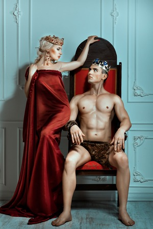 subjugation: Man sits on the throne and looks at the queen. Crown on their heads. Stock Photo
