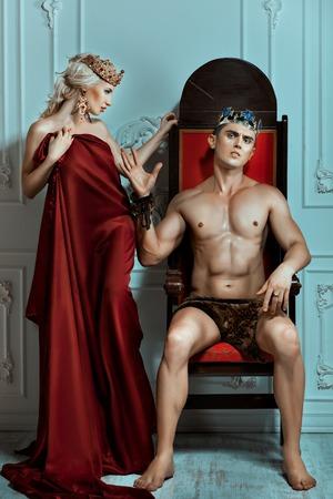 siervo: El rey se sienta en un trono con la cara altiva. La mano rechaza la reina. Foto de archivo