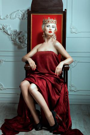 Mujer con una corona en la cabeza sentado en el trono. La Reina mirada arrogante. Foto de archivo