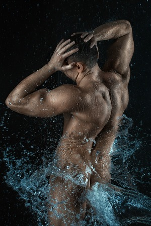 Wet body of a man from the back. Splash water on his naked body.