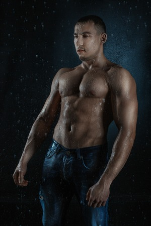 aqua naked: Wet athlete body bodybuilder in the rain. Black background, drops of water. Stock Photo