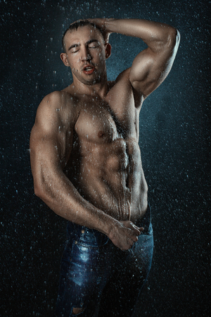 aqua naked: Drops of water falling on the body of a man.  Man model posing for fashion.
