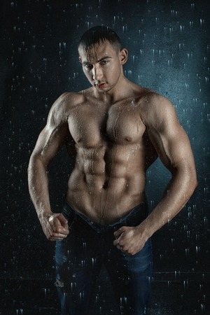 aqua naked: Water flows on the embossed male body builder. Around the flying drops of water splashes on the body.