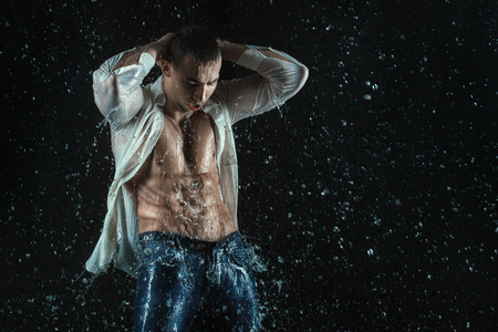 aqua naked: Man with a beautiful figure. Man around wet fly spray of water.