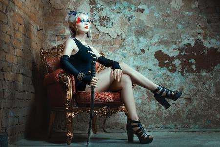 Frau sitzt auf einem Stuhl, ein Schwert in der Hand. Auf dem Gesicht des Krieges zu malen. Standard-Bild - 50886422