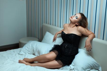 pechos: Mujer en un vestido con los hombros descubiertos que se sientan en la cama. Foto de archivo