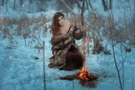 Girl shaman is heated by the fire in winter in the forest. Blizzard sweeps, and it is snowing.
