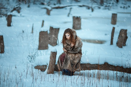 froze: Girl froze in the winter woods. Around covered with snow and it is cold. Stock Photo