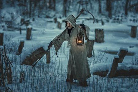 imminence: Segador severo con una guadaña está en el campo. En invierno, la nieve viene.