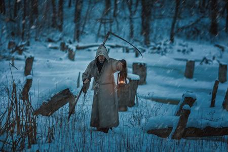 imminence: Nieve en el campo es el hombre con la guadaña de la muerte. Está vestido con una sudadera con capucha y las causas de terror. Foto de archivo