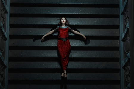 fainted: Gothic girl fell on the stairs at night. It is a strange and suggestive horror and fear. Stock Photo