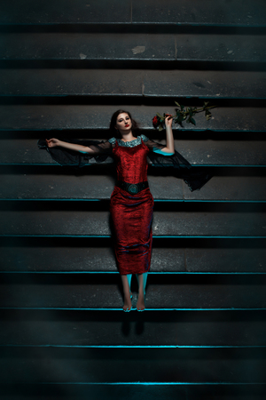 fainted: Girl with a red rose lying on the stairs at night. This gothic and strikes fear and terror. Stock Photo
