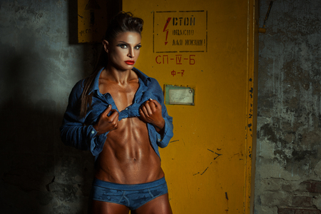 life threatening: Woman bodybuilder demonstrates body. It is next to the electrical closet on which is written life threatening.