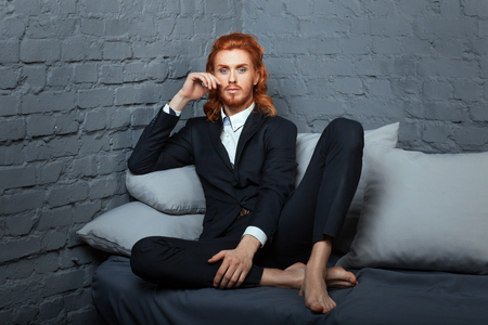 frizz: On the sofa sits cross-legged guy. On his head red hair and a red beard.
