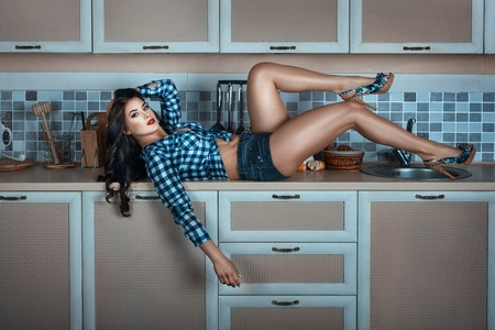 Beautiful girl lying on the kitchen table. She is wearing a shirt and shorts, bare his feet. Stock Photo