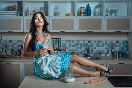 erotically: Girl is holding a glass of milk, she sits at the kitchen table. She wore an apron housewife. Stock Photo