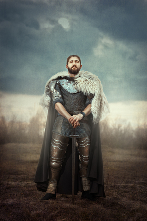 fortitude: The courageous knight dressed in chain armor standing in a field leaning on his sword.