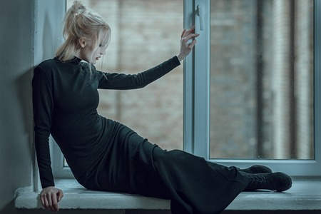 Blonde woman lying on the window sill and sad, her unhappy.