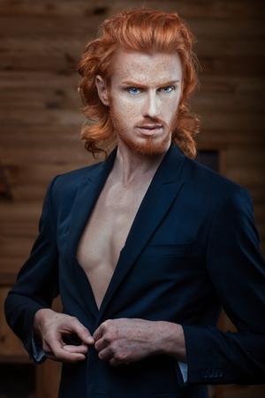 homme nu: L'homme porte une veste sur son corps nu, ses cheveux rouge feu. Banque d'images