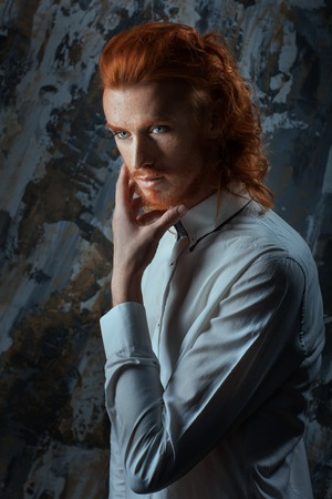 vogue style: Portrait of a man with fiery curls on his head on the face of freckles.