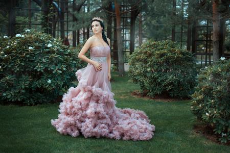 La reina en un vestido de color rosa magnífica está caminando en el jardín entre los árboles.