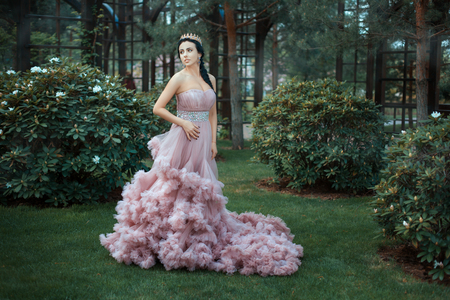 The Queen in a magnificent pink dress is walking in the garden among the trees. Stock Photo