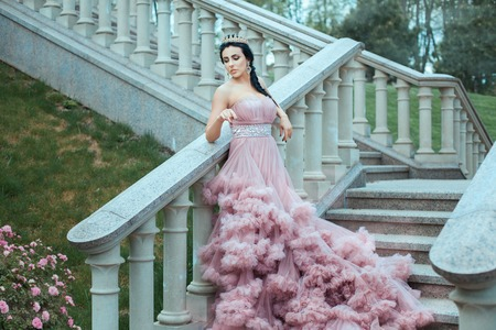The young queen in a lush pink ball gown standing on the stairs of the castle. Stock Photo