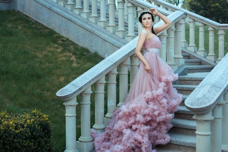 slinky: The young queen dressed in a delicate pink dress is walking up the stairs of the castle.
